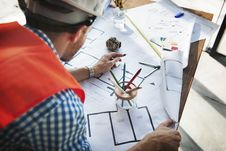 Free Man Wearing White Hard Hat Leaning On Table With Sketch Plans Royalty Free Stock Images - 126180629
