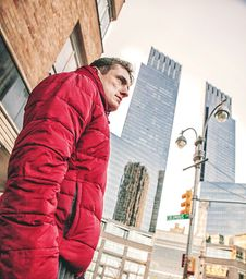 Free Man Wearing Red Bubble Coat Standing Under Tall Buildings Stock Image - 126180801