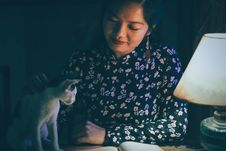 Free Woman Caressing A Cat While Reading Book Lighted By A Table Lamp In Dark Royalty Free Stock Photos - 126180878