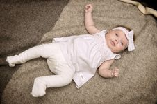 Free Baby In White Dress Laying On Gray Textile Royalty Free Stock Images - 126180919