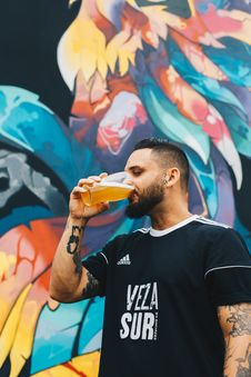 Free Tattooed Man Drinking On Clear Drinking Glass In Front Of Multicolored Painted Wall Stock Photography - 126181852
