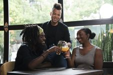 Free Three Persons Cheers With Clear Glasses Filled With Liquid Beverages Near Window Royalty Free Stock Photography - 126182087