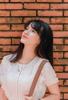 Free Woman Standing In Front Of Brick Wall Looking Up Royalty Free Stock Image - 126182116