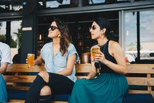 Free Woman In Black And Blue Sleeveless Dress Holding Glass Of Beer Sitting On Bench Stock Images - 126182124