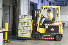 Free Man Riding A Yellow Forklift With Boxes Royalty Free Stock Photo - 126182175