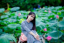 Free Woman Sitting On Brown Chair Surrounded With Lotus Flowers Royalty Free Stock Images - 126182339