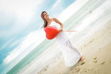 Free Woman Holding A Heart-shaped Balloon Standing On Seashore Royalty Free Stock Images - 126182379