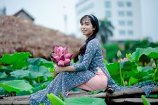 Free Woman Holding Pink Petaled Flowers Sitting On Brown Wooden Panel Stock Photos - 126182423