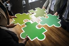 Free Four People Holding Four Jigsaw Pieces On Top Of Brown Wooden Table Royalty Free Stock Image - 126182596