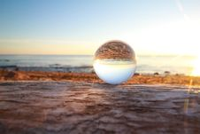 Free Clear Marble Toy Reflecting Seashore During Golden Hour Royalty Free Stock Photo - 126183045