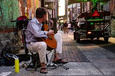 Free Man Sitting Playing Classical Guitar On Gray Road Royalty Free Stock Photos - 126183298