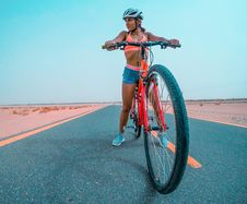 Free Woman Riding Red Mountain Bike On Asphalt Road Stock Image - 126183431