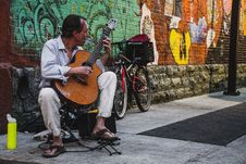 Free Man Seated And Playing Brown Classical Guitar On The Street Stock Photo - 126183620