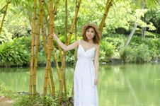 Free Woman In White Spaghetti Strap Dress Holding On Bamboo Tree Near Body Of Water Stock Photos - 126183633