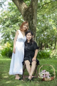 Free Smiling Woman Standing Beside Smiling Woman Sitting On Folding Stool Under Tree Stock Photo - 126183820