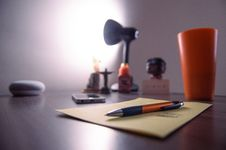 Free Retractable Pen On Perer Near, Plastic Cup, Smartphone, And Lamp On Desk Royalty Free Stock Image - 126183876