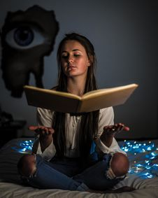 Free Woman Reading A Book Sitting On Mattress Near The Blue String Light Inside The Room Stock Photography - 126184182