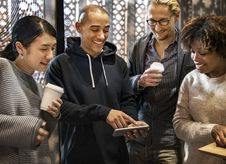 Free Group Of Men And Women Smiling While Looking At Phone Stock Photo - 126184250