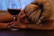 Free Woman With White Flower-accent Headdress Leaning Her Head On Table Beside Half-filled Wine Glass Stock Photography - 126184252
