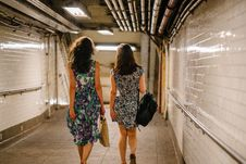 Free Two Women Carrying Bags While Walking In Tunnel Royalty Free Stock Photos - 126184278