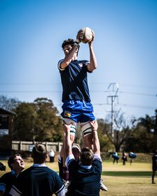 Free Two Men Carrying Standing Man Holding Rugby Ball Over Field With People Across Electric Post Under Blue Sky Royalty Free Stock Images - 126184749