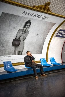 Free Man Sitting On Blue Chair In Front Of Mauboussin Signage Royalty Free Stock Images - 126184889