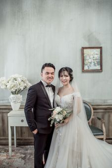 Free Man And Woman Taking Wedding Photo Inside Gray Concrete House With Wall Arts And Flowers On Vase Stock Photos - 126185093