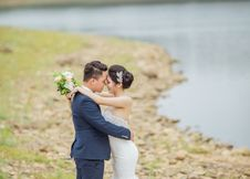 Free Newly Wed Coupe Standing Near Body Of Water Royalty Free Stock Images - 126185139