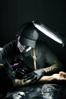 Free Tattoo Artist In Black Gloves Drawing A Tattoo On A Person S Arm Royalty Free Stock Photos - 126186268