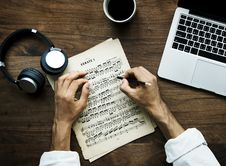 Free Person Writing On Beige Musical Note Beside Laptop Stock Photos - 126186463