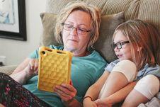Free Woman Holding Tablet Lying Beside Girl Wear Eyeglasses Royalty Free Stock Image - 126186546