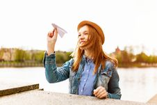 Free Woman In Blue Denim Button-up Jacket And Brown Hat About To Fly A Paper Plane Beside A Body Of Water Royalty Free Stock Photos - 126187398