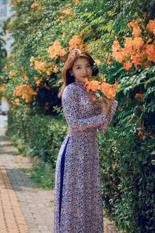 Free Women S Blue, White, And Purple Long-sleeved Maxi Dress Standing Beside Orange Flowers Royalty Free Stock Photography - 126187797