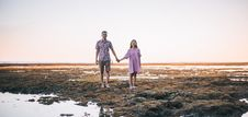 Free Woman And Man Holding Hands While Walking On Soil Near Water Stock Photography - 126188132