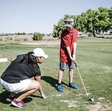Free Boy Holding Golf Club In Front Of Crouching Woman Stock Photo - 126188580