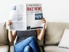 Free Person Reading The Daily Fake News Newspaper Sitting On Gray Couch Royalty Free Stock Images - 126188799