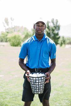 Free Man Holding Basket Of Golf Balls Stock Image - 126188961