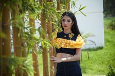 Free Woman Wearing Black And Yellow Crop Top Holding Bamboo Stock Images - 126189054