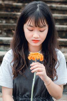 Free Girl Holding Orange Gerbera Daisy Stock Images - 126189094