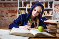 Free Woman Wearing Blue Jacket Sitting On Chair Near Table Reading Books Royalty Free Stock Image - 126189196