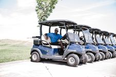 Free Man In Blue Shirt And Black Shorts Outfit Riding On Blue Golf Cart Stock Photography - 126189202