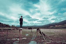 Free Man Standing On Brown Wooden Stand With Mountain At Distance Stock Images - 126189654