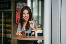 Free Woman Sitting At Table Holding Ice Cream Royalty Free Stock Images - 126189749