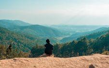 Free Man Sitting On Cliff Overlooking Mountain Stock Image - 126189811