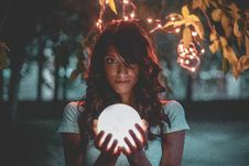 Free Woman Holding Lighted Glass Ball Under String Lights Stock Image - 126189881