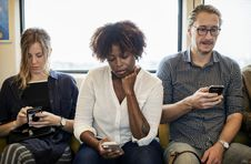 Free Two Women And One Man Sitting In Front Of Window Using Smartphones Stock Image - 126190841