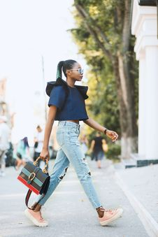 Free Woman In Blue Crop-top And Distressed Blue Denim Jeans Holding Black Handbag Walking On Road Stock Photography - 126191032