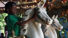 Free Boy Wearing Green Polo Shirt Riding Carousel Stock Photography - 126191132