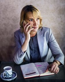 Free Woman Calling While Sitting In Front Of Desk Behind The Wall Stock Photos - 126191493