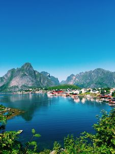 Free Large Body Of Water Across Village And Mountains Under Blue Skies Stock Image - 126192011